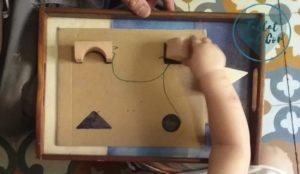 Mano de niña emparejando las figuras con sus sombras pintadas en cartón