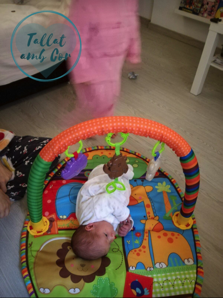 Bebé de una semana en colchoneta-gimnasio