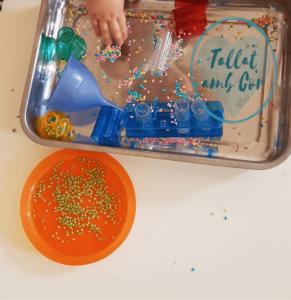 Bandeja metálica con recipientes rojo, amarillo, azul y verde y otros 3 transparentes, un embudo, y arroz teñido en los colores mencionados