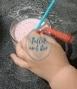 Manos de bebé de 22 meses poniendo dos pajitas en un vaso con batido de plátano y frambuesas