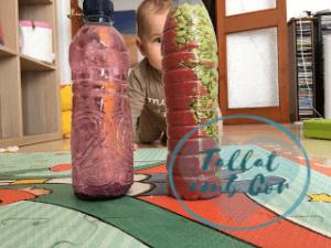 Dos de las botellas sensoriales, la de agua y purpurina y la de piedras y arena en primer plano. Detrás se ve a un bebé en posición de gateo mirándolas