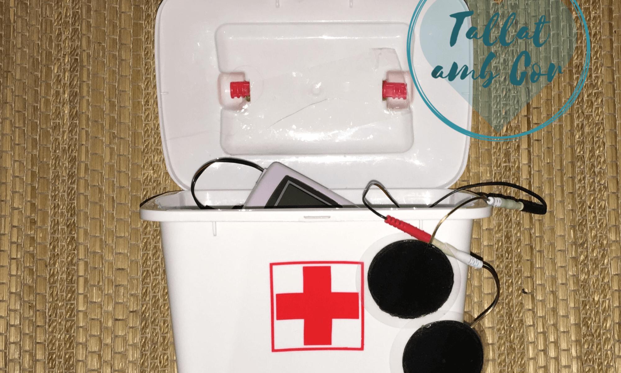 Botiquín blanco abierto con cruz roja y del interior asoma unos electrodos de un TENS, aparato usado en rehabilitación