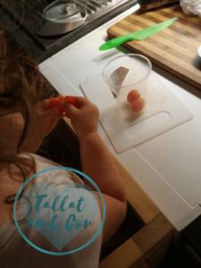 Bebé de 22 meses comiendo tomates Cherry durante la preparación de la receta