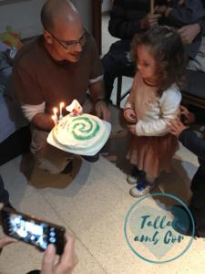 Laia con su padre y la tarta con sus 3 velas, la espiral del corazón de Te Fiti y la imagen de Vaiana y Maoui en un barquito.