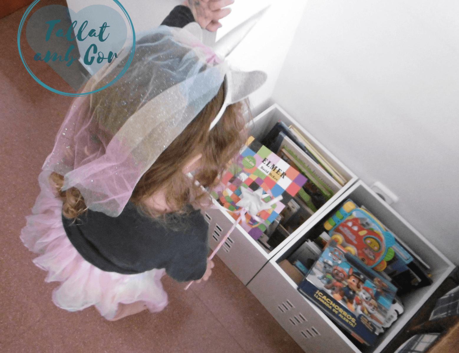 Montessori y fantasía: Vista desde detrás, niña con diadema de unicornio, tutú y varita tocando libro de Elmer