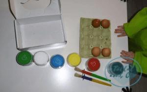 Manos de bebé de dos años, los 4 huevos vacíos en la huevera y material para pintar el fondo: pinceles y pintura de dedos