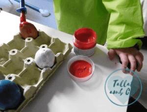 Manos de niña de dos años pintando los huevos con las pinturas de dedos y el pincel