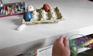 Otro plano de manos de bebé de dos años decorando con un rotulador los huevos de Pascua pintados con pintura de dedos