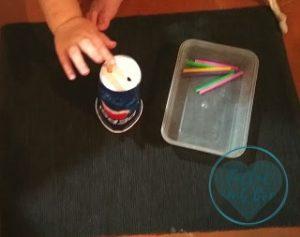 Mano de bebé introduciendo objetos (pajitas) por los agujeros de un vaso de cartón