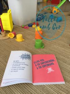 """Fondo con juguetes en el suelo y en primer plano libro abierto en el que se lee """"Tú ves: el desorden de casa, las veces que has perdido la paciencia, cuando llegáis tarde"""" y otros. En la otra página """"ellos ven: a su superheroína, a su supermamá"""""""