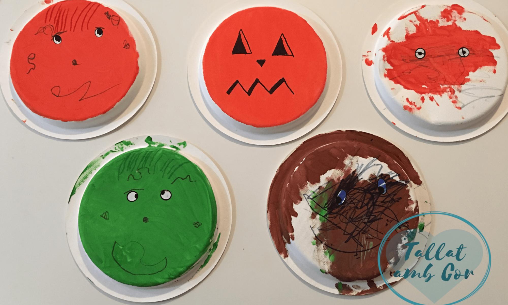 5 platos pintados 3 de color naranja, 1 marrón y 1 verde. Todos ellos con caras pintadas.