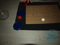 Cartón con contornos de distintos tamaño de tapón dibujados y, al lado, los tapones correspondientes