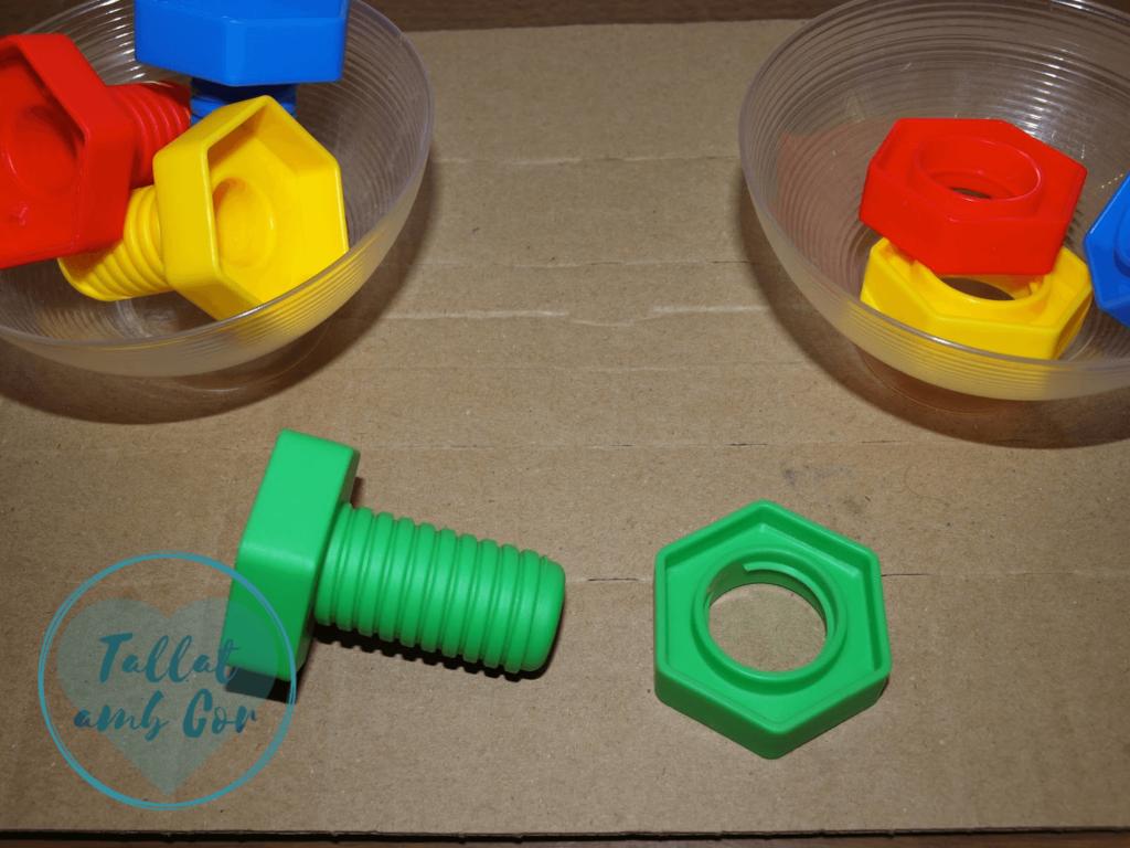 Misma visión superior con los dos boles, pero con la tuerca y tornillo de color verde delante de ellos