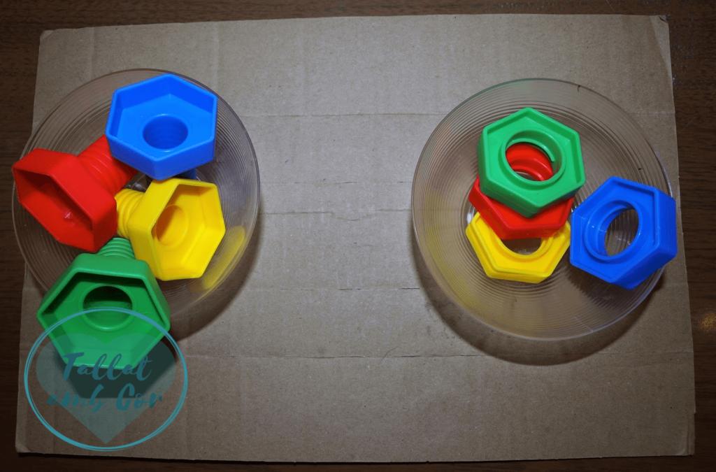 Dos boles vistos desde arriba sobre una bandeja. Un bol contiene 4 tornillos de juguete de distintos colores con cabeza hexagonal y el otro las tuercas que les corresponden, de los mismos colores y hexagonales
