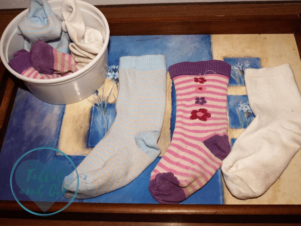 3 calcetines sobre una bandeja en la que también hay un recipiente con las parejas de esos calcetines