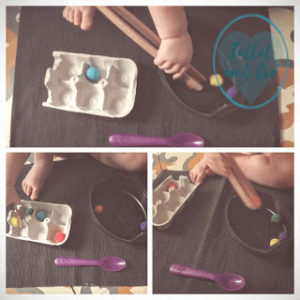 Manos de bebé de 20 meses cogiendo pompones con unas pinzas de madera y colocándolos en una huevera