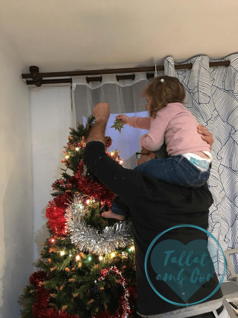 Niña de 3 años sobre los hombros de su padre colocando la estrella en lo alto del árbol del Navidad