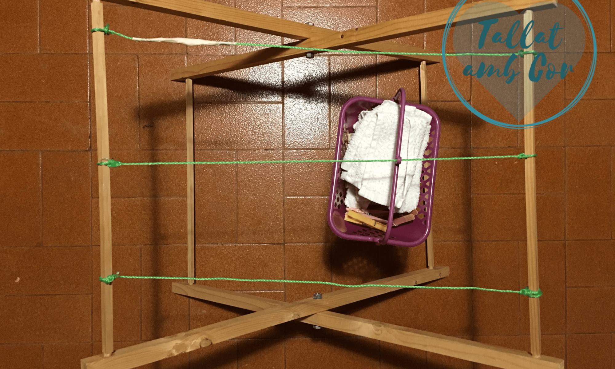Vista superior del tendedero infantil hecho en casa con cesta colgando de uno de los hilos.